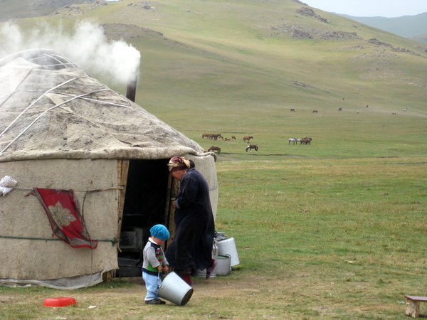A woman entering her yurt on the shore of the alpine Lake Song Kol, Kyrgyzstan