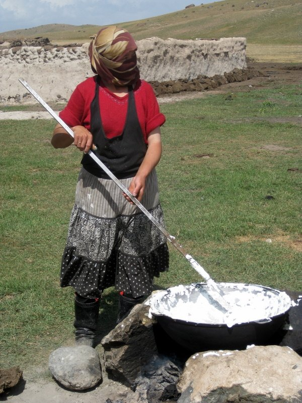 Woman making qurut at farmstead in mountains near Sary Moghul, Kyrgyzstan