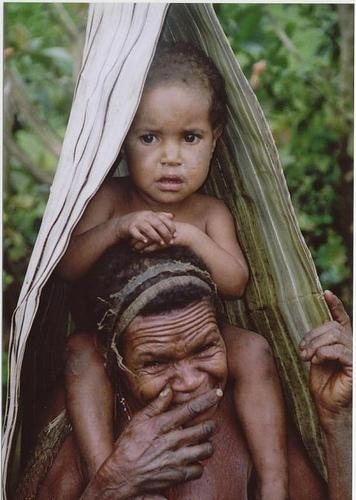 Woman of the Yali tribe with three chopped-off fingers and a child under portable rain shelter, Waniyok village, the Yalimo, Central Highlands, West Papua
